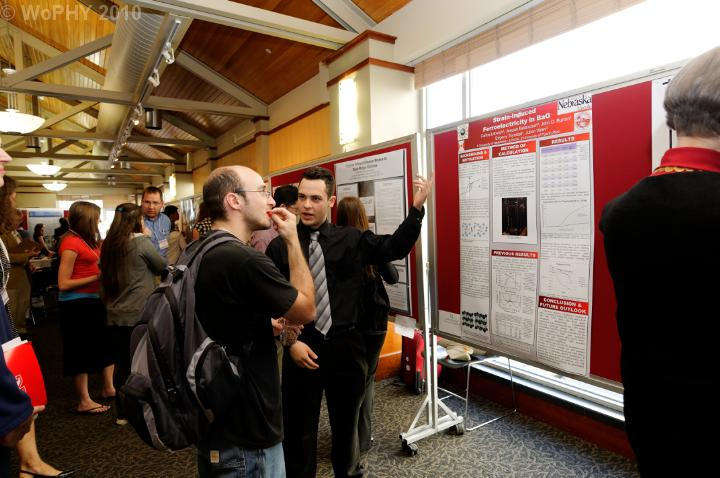 Alex Stamm watches a student poster presentation