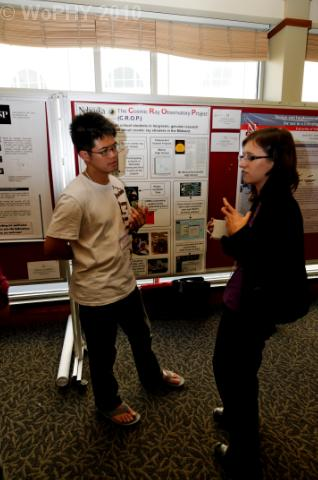 Wayne Huang listens to student poster presentation